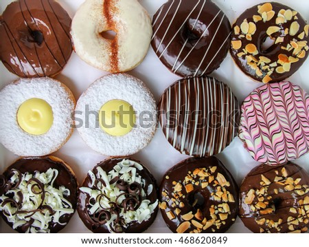 Assorted donuts in a box with chocolate