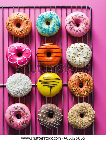 Assorted donuts with different fillings on pink background - stock photo