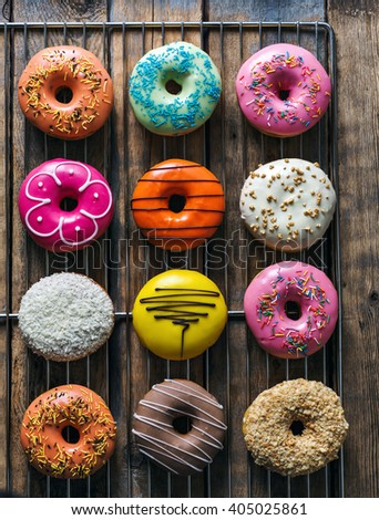 Assorted donuts with different fillings on wooden background - stock photo