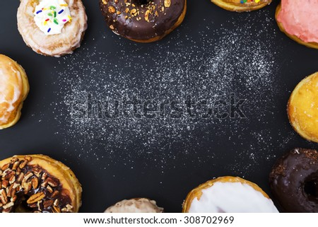Assorted donuts with powder flour on black background - stock photo