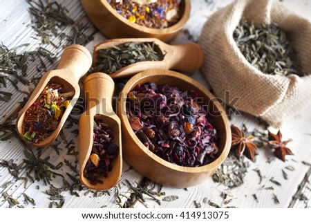 Assorted dried tea leaves on wooden background - stock photo