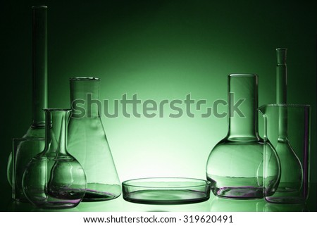 Assorted empty laboratory glassware, test-tubes. Green tone medical background. Copy space