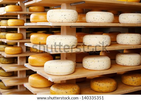 Assorted flavours of cheese wheels maturing on rows of wooden shelves in a cheese factory - stock photo