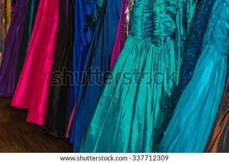 Assorted formal dresses in different colors for sale in retail store.  Prom gown and wedding dress detail, perfect for fashion trends and business blog and website - stock photo
