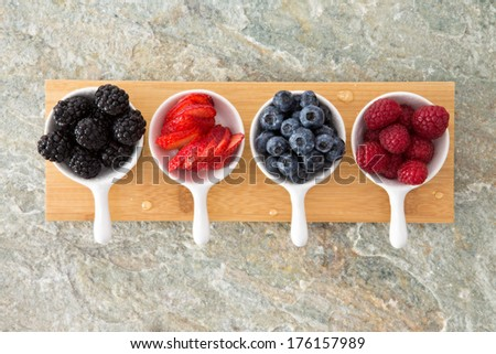 Assorted fresh berries in taster dishes viewed from above lined up on a wooden board on a stone kitchen counter with blackberries, sliced strawberry, blueberries and raspberries - stock photo