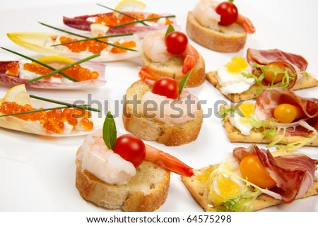 Assorted fresh canapes on tray ready for holiday table over white background - stock photo