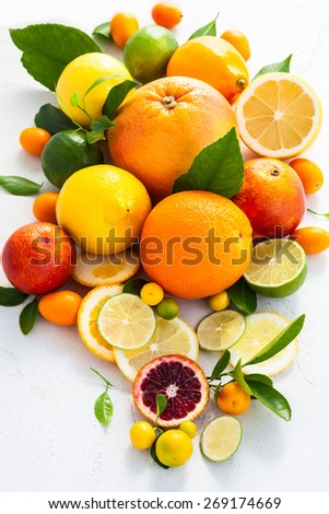Assorted fresh citrus fruits with leaves. - stock photo