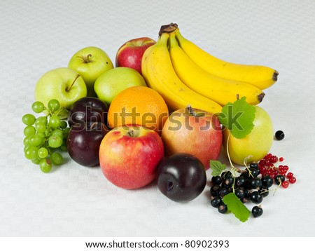 Assorted fresh fruit on pale checkered table cloth - stock photo