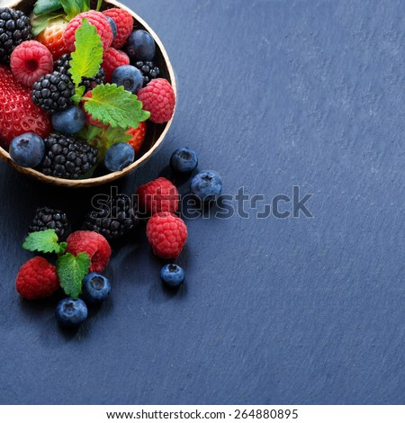 Assorted fresh garden berries on a black background, space for text, close-up - stock photo