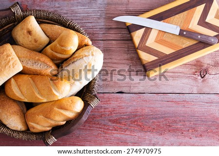 Assorted fresh rolls in a basket ready to be served for dinner standing on a rustic wooden table alongside a decorative inlaid wood cutting board and knife, overhead with copy space - stock photo