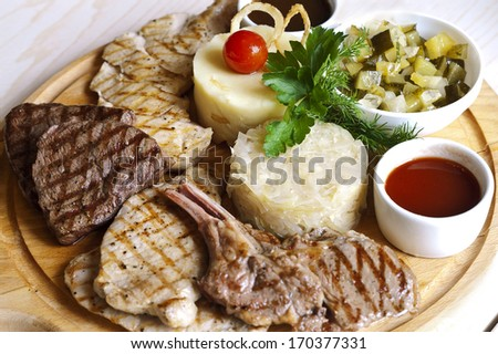 assorted fried meat laid on the wooden tray, overhead shot focused on center