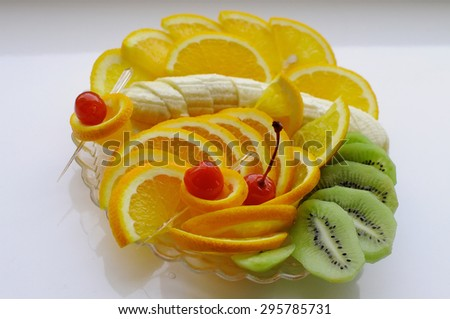 Assorted fruit on a plate. Sliced banana, orange and kiwi lie on a transparent plate. Soft light from the window. - stock photo