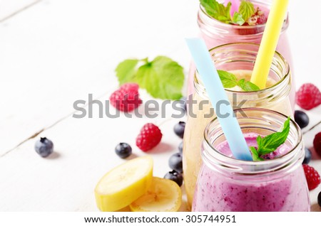 Assorted fruit shakes on white table. Smoothie concept. Space for text
