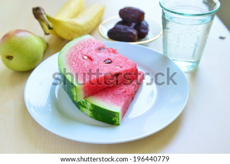 Assorted fruits and slices of fresh watermelon with glass of drinking water. - stock photo