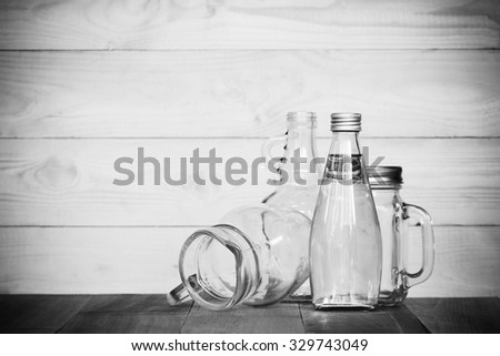 assorted glass bottles on a white washed wooden table. Clear glass bottles and containers of various sizes and shapes. Black & white.