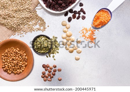 Assorted grains, dried raisins, hazel and macadamia nuts displayed on a white surface for a healthy vegetarian diet or cooking ingredients, overhead view with copy space - stock photo