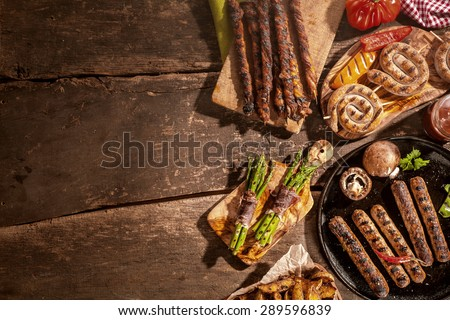 Assorted grilled food including sausages, potato wedges and asparagus bacon wraps from a summer barbecue on a rustic wooden picnic table with copyspace - stock photo