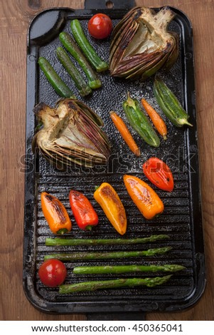 Assorted grilled vegetables - zucchini, asparagus, artichokes, mini pepper, jalapeno, tomatoes, and carrots - on griddle.