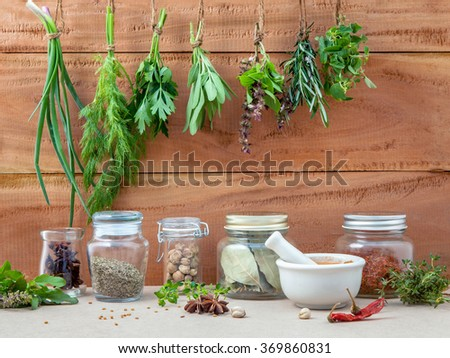 Assorted hanging herbs ,parsley ,oregano,sage,rosemary,sweet basil,dill,spring onion  and  set up with dry and fresh thyme,chili,bay leaves,white mortar  and star anise  on old wooden background. - stock photo