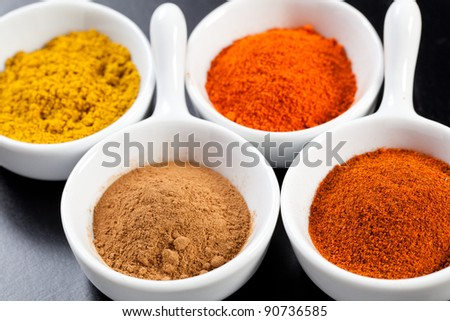 Assorted hot spicy powders in white bowls over black table - stock photo