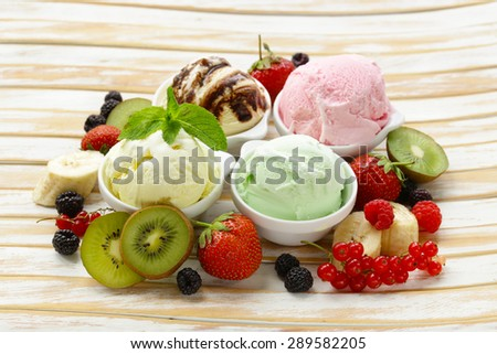 Assorted ice cream (strawberry, banana, mint, chocolate) and fresh berries on the wooden table - stock photo