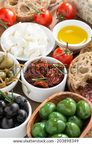 assorted Italian antipasti - olives, pickles and bread, top view, vertical - stock photo