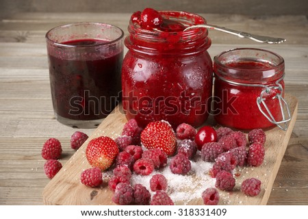 Assorted jams in glass jars and fresh berries in sugar on wooden cutting board. - stock photo