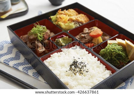 Assorted Japanese food, bento box served in a wooden box. - stock photo