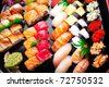 Assorted japanese sushi on a black plate. - stock photo