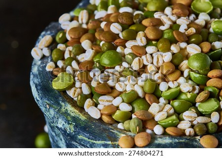 Assorted legumes and cereals on dark background - stock photo