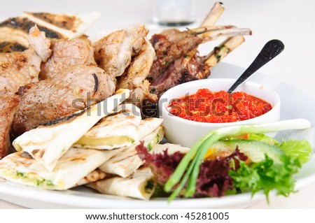 Assorted meat grilled with pita, herbs and spicy sauce
