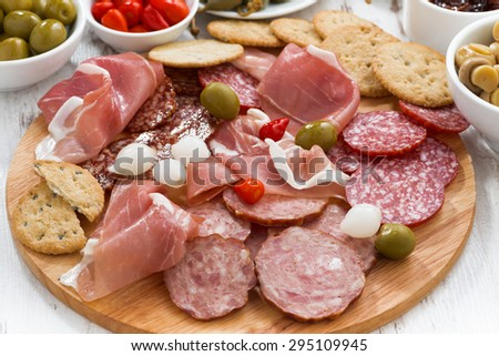 Assorted meat snacks, sausages and pickles on wooden board, close-up, horizontal - stock photo