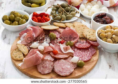 Assorted meat snacks, sausages and pickles on wooden board, horizontal - stock photo