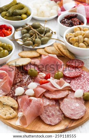 Assorted meat snacks, sausages and pickles, vertical, close-up, top view - stock photo
