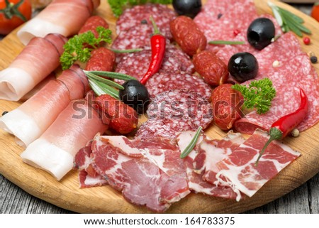 Assorted meats and sausages, olives and spices, close-up, horizontal - stock photo