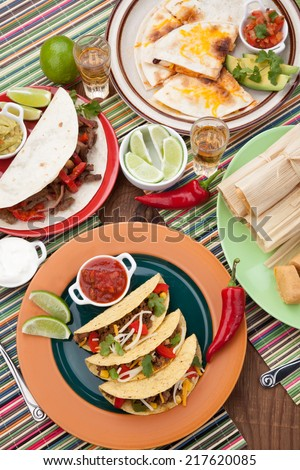 Assorted Mexican dishes, with whole grain corn beef tacos as the main subject.  - stock photo