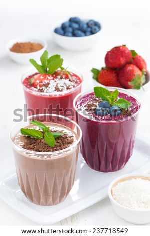 Assorted milkshakes - strawberry, blueberry and chocolate and ingredients, vertical, close-up - stock photo