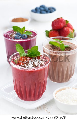 Assorted milkshakes - strawberry, chocolate and blueberry, close-up, vertical - stock photo