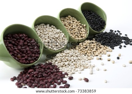 Assorted mixed dried beans spilling in green ceramic dish - stock photo