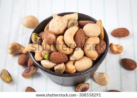 Assorted mixed nuts in bowl on the table - stock photo