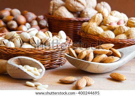 Assorted nuts in baskets: walnut, pistachios, almond, peanut, hazelnut, pine nuts