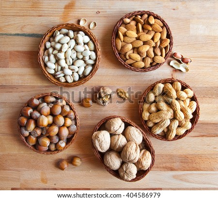 Assorted nuts in bowls: walnut, pistachios, almond, peanut, hazelnut - stock photo