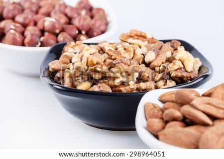 Assorted nuts in ceramic bowls on white background - stock photo