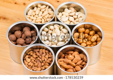 Assorted nuts in Iron pot  pecan, pistachios, almond, peanut, cashew,Pine nuts  - stock photo