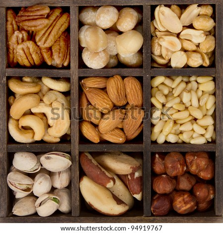 assorted nuts nine varieties for a background in a printers box, almond, cashew, brazil, hazelnut, peanut, pecan, pine, pistachio, macadamia - stock photo