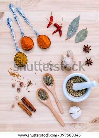 Assorted of dried spices white pepper,cumin ,bay leaf,cinnamon,star anise,thyme,ginger ,chili ,garlic ,rosemary and fennel seeds with white mortar on wooden background. - stock photo