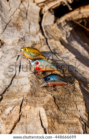 Assorted of various kind of fishing baits on the natural background. Objects on the  old tree with brown bark. - stock photo