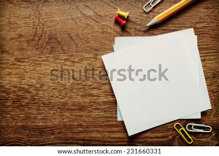 Assorted Office Supplies such as Clean Papers, Pencil, Thumbtacks and Clips on the Wooden Table, Resting at the Bottom Edge with Copy Space Above for Texts. - stock photo