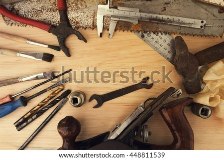 Assorted old tools on light wooden background. Pliers, wrenches, drills, screwdriver, ruler - stock photo