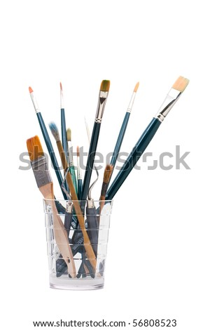 Assorted paintbrushes and painting tools in glass - stock photo